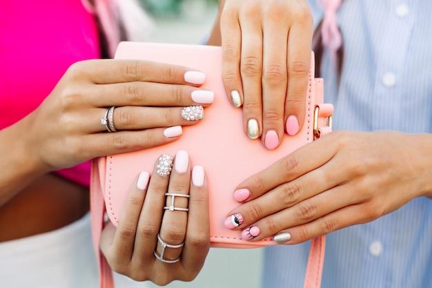 Feche de saco com mãos de meninas com manicure por cima.