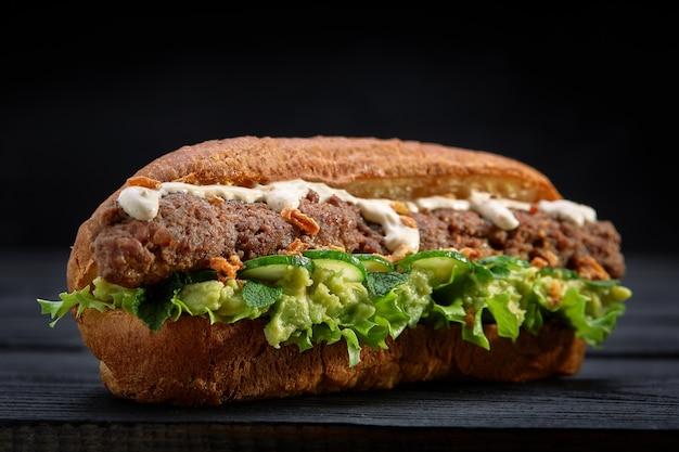 Feche de sanduíche de kebab em fundo preto de madeira. conceito de fast food