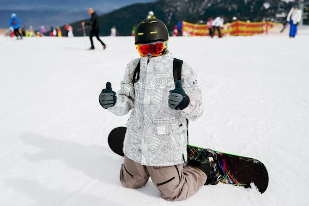 Feche de snowboarder ajoelhado na neve com polegares para cima e olhando para a câmera.