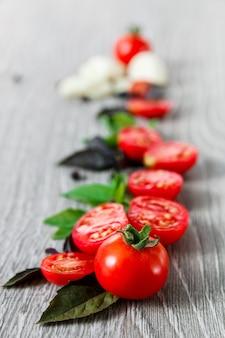 Feche de tomate cereja, alho e manjericão fresco em fundo cinza de madeira. quadro, armação. copie o espaço.