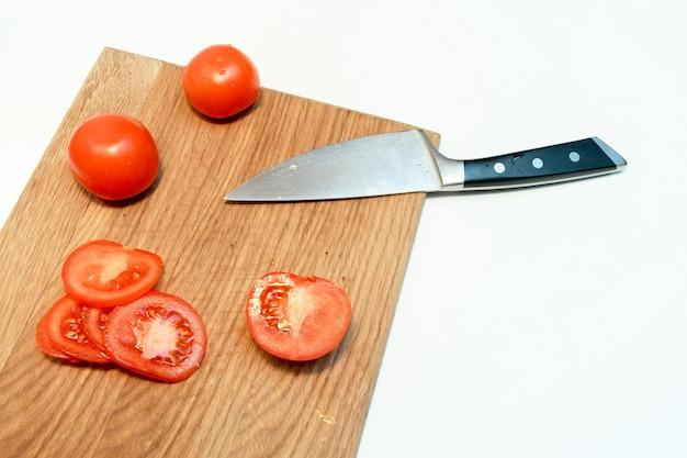 Feche de tomates maduros frescos picados e faca em uma tábua de madeira em uma cozinha em casa.