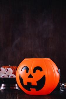 Feche de truques de halloween assustadores, conceito de decoração de festival de terror, lanterna de abóbora com castiçal e fumaça.
