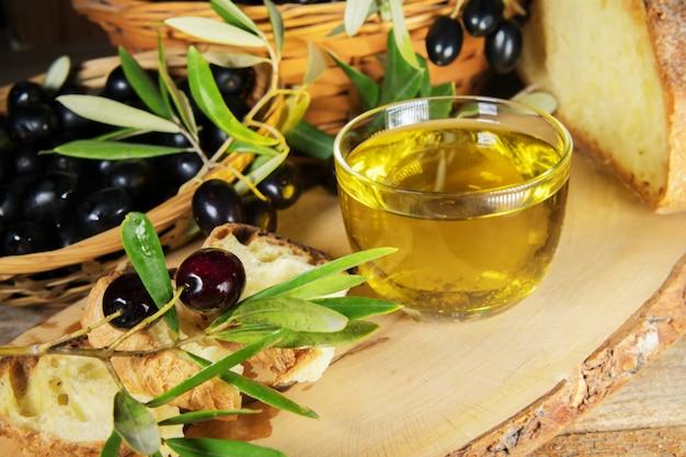 Feche de uma tigela de vidro cheia de azeite com pão e brunches de azeitona. gorduras saudáveis