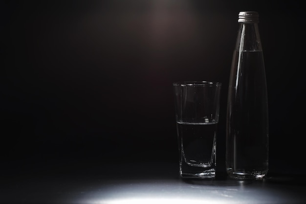 Feche derramando água purificada da garrafa na mesa na sala de estar. água potável. água com vitaminas minerais. água saudável, rica em minerais e refrescante.