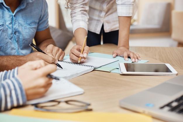 Feche detalhes da equipe trabalhando o novo projeto no espaço de coworking, escrevendo idéias, olhando através de gráficos no tablet e laptop. trabalho em equipe, conceito do negócio.