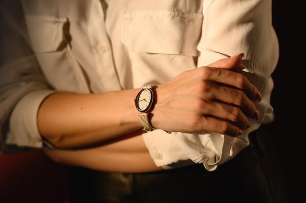 Feche detalhes da moda, mulher de negócios jovem usando relógio dourado e camisa branca. acessórios ideais para o outono.