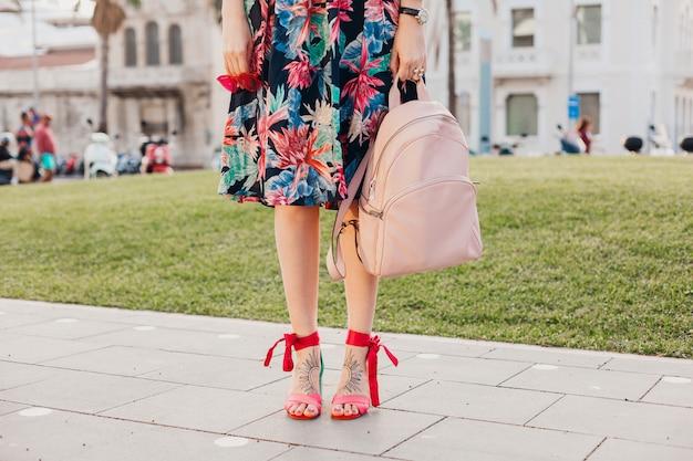 Feche detalhes das pernas em sandálias rosa de mulher estilosa andando na rua com saia colorida estampada, segurando uma mochila de couro rosa