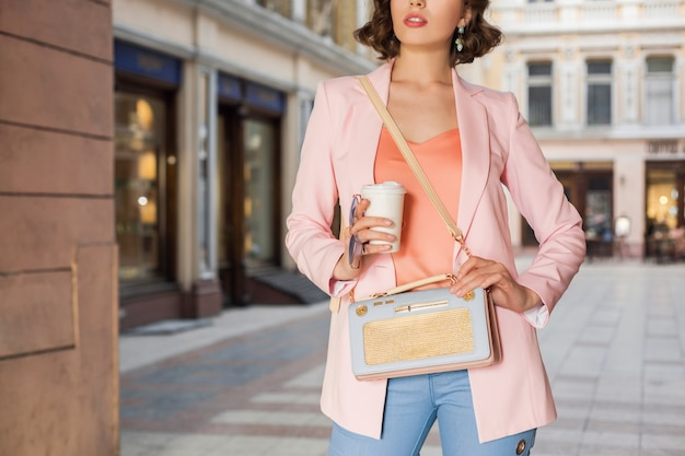 Feche detalhes de acessórios de mulheres em roupas elegantes, andando na rua, óculos de sol, bolsa, jaqueta rosa, cores da moda, tendência da moda primavera-verão, estilo elegante, bebendo café