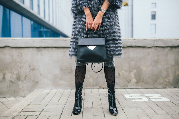 Feche detalhes de acessórios de uma mulher elegante andando pela cidade com um casaco de pele quente, inverno, clima frio, segurando uma bolsa de couro, pernas em botas, calçados, tendência da moda de rua