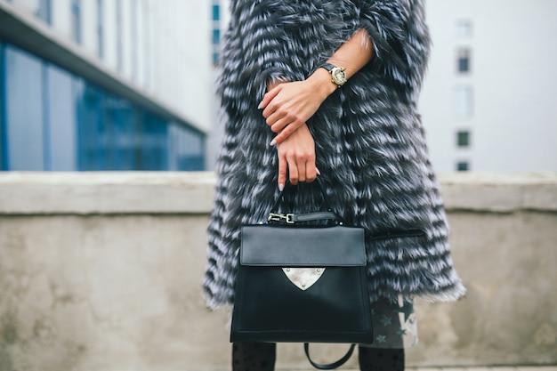 Feche detalhes de acessórios de uma mulher elegante caminhando pela cidade com um casaco de pele quente segurando uma bolsa de couro preta