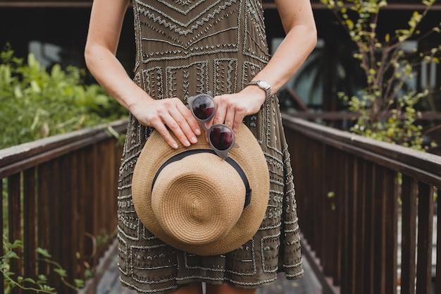 Feche detalhes de mãos segurando um chapéu de palha e óculos de sol, acessórios elegantes, jovem mulher atraente em um vestido elegante, estilo de verão, tendência da moda, férias, posando em uma villa tropical, sorrindo, feliz