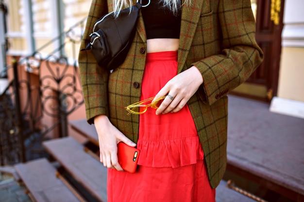 Feche detalhes de moda de mulher posando na rua perto de loja de luxo, vestindo top crop, jaqueta grande e saia vermelha feminina, segurando óculos escuros e o telefone dela, empresária moderna.