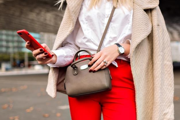 Feche detalhes de moda, mulher de negócios, bateu em algo em seu telefone, fundo urbano da cidade de outono, terno brilhante e casaco de caxemira, pronto para a conferência.