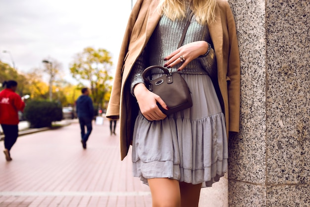 Feche detalhes de moda, mulher na rua, primavera, vestido de seda e casaco de caxemira, suéter prata e bolsa de corpo cruzado, roupa elegante e glamour feminina