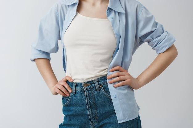 Feche detalhes de roupas elegantes de jovem estudante de mãos dadas na cintura, vestindo camiseta branca sob a camisa azul e jeans.