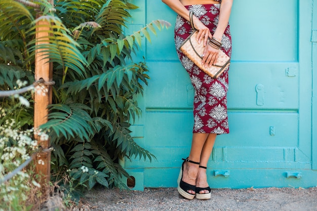 Feche detalhes de sandálias de calçado em uma cunha de mulher bonita e elegante posando na parede azul, estilo de verão, tendência da moda, saia, skinny, bolsa de palha, acessórios, férias tropicais, pernas