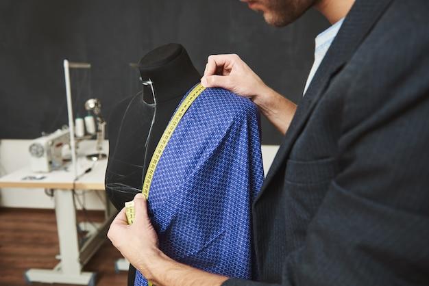Feche detalhes do talentoso profissional jovem caucasiano masculino designer trabalhando no vestido novo para a coleção de primavera, verificando tamanhos com fita métrica, passando o dia em sua oficina