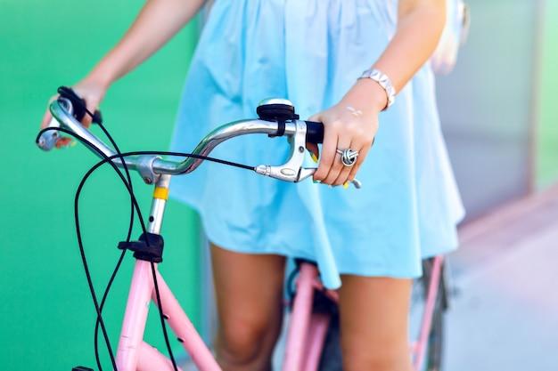 Feche detalhes jovem andando de bicicleta vintage na rua, vestido fofo, humor moderno de viagens