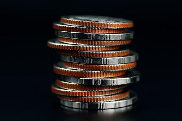 Feche diferentes tipos de moedas empilhadas em um fundo preto e economize dinheiro para negócios ou finanças