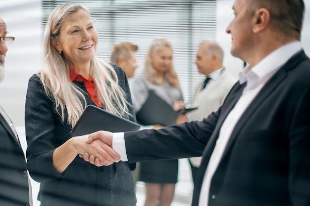 Feche dois empresários apertando as mãos no saguão do escritório