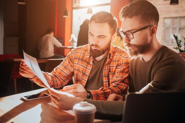 Feche dois empresários descolados que procuram papéis e aprendem informações com eles. eles estão se preparando para uma reunião de negócios. cortar vista.