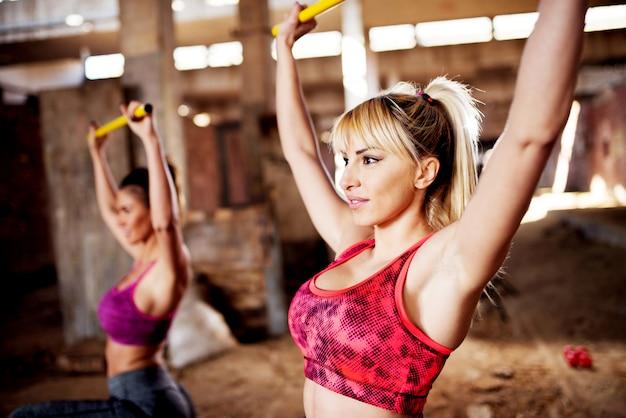 Feche duas cabem meninas exercitando agachamentos com barras no hangar.