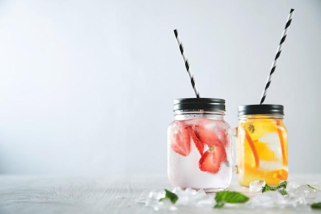 Feche duas limonadas caseiras frescas feitas de água com gás, gelo, morango e laranja. gelo derretido e folhas de hortelã ao redor, canudinhos listrados dentro de potes rústicos.