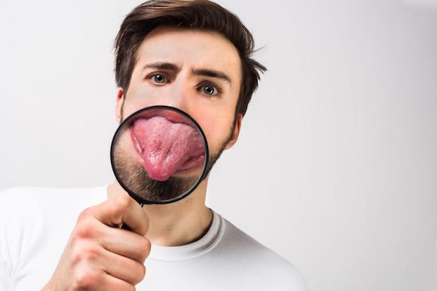 Feche e corte a vista de um cara mostrando sua língua através da lupa. ele está tentando se divertir e não ser chato. isolado na parede branca