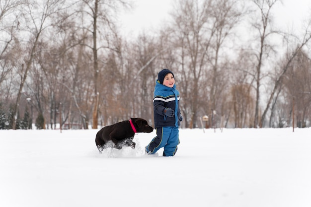 Feche e uma criança feliz brincando na neve