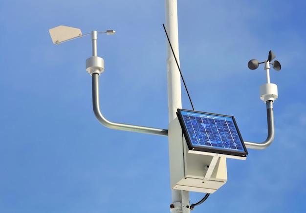 Feche em um anemômetro com painel solar no céu azul