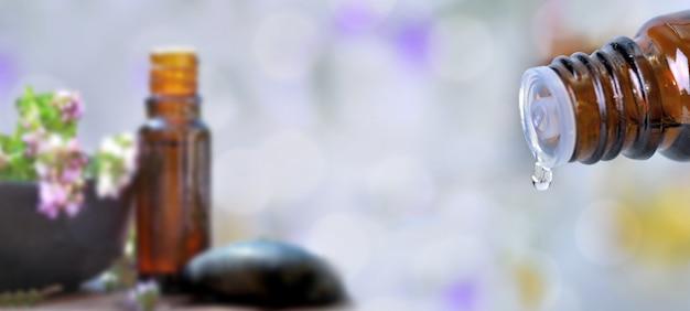 Feche em uma garrafa de óleo essencial, derramando óleo em blury fundo em tamanho panorâmico