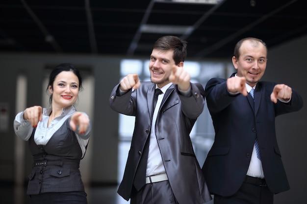 Feche. equipe de negócios bem-sucedida apontando para você
