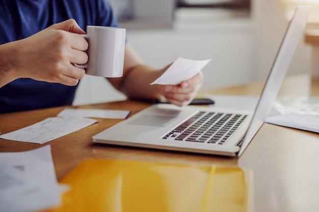Feche f homem sentado em casa, segurando a caneca com café e pagar contas online.