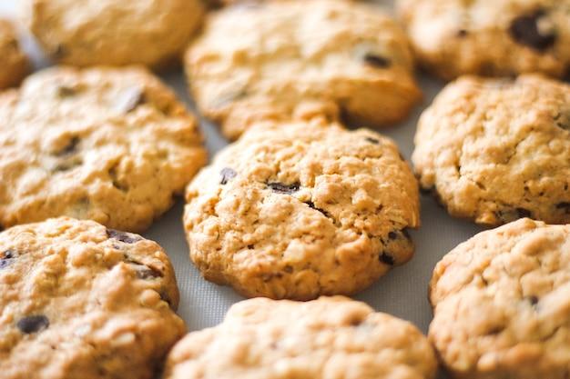 Feche fileiras de saborosos biscoitos de aveia caseiros com gotas de chocolate. bolos de aveia marrons na mesa branca, produtos caseiros doces e saudáveis