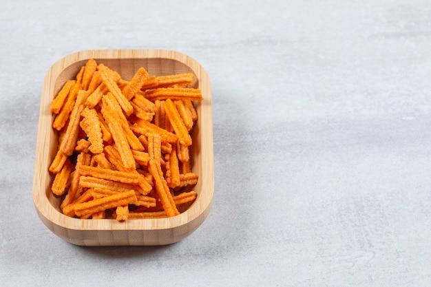 Feche foto de batatas fritas frescas em uma tigela de madeira.