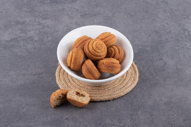 Feche foto de biscoitos caseiros em uma tigela branca.