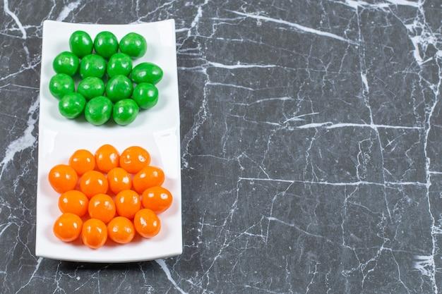 Feche foto de bolas de doces coloridas na chapa branca.