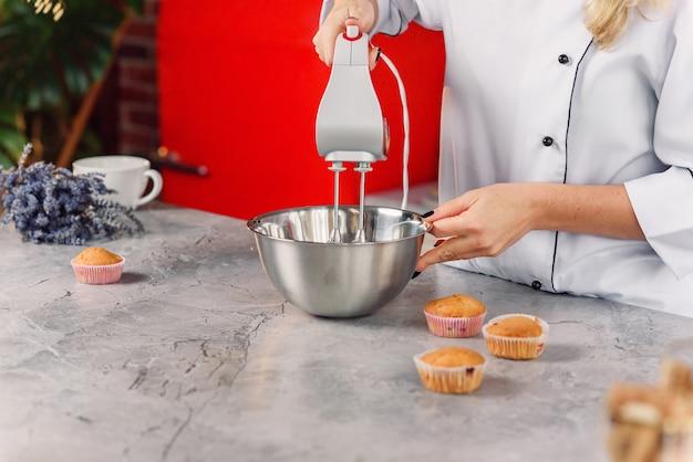 Feche foto de confeiteiro feminino mistura um creme de leite fresco em uma placa de metal profunda com um misturador de cozinha vermelho.