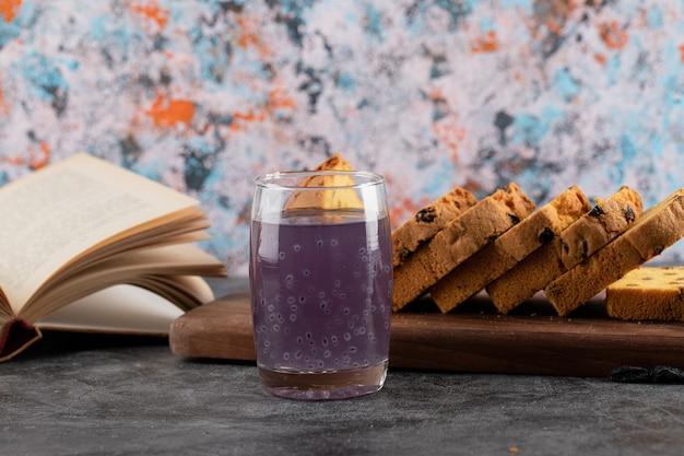 Feche foto de coquetel de uva fresca com bolo fatiado e livro.