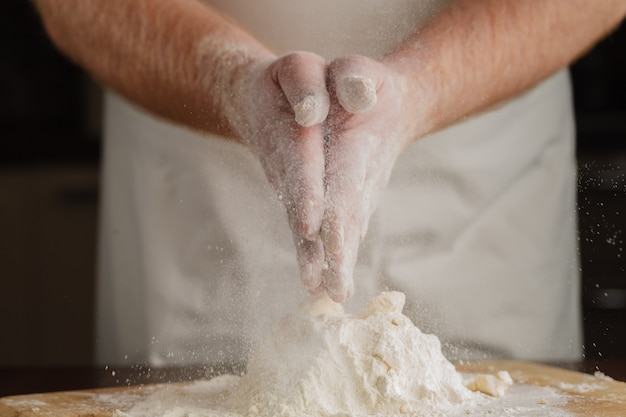 Feche foto de farinha nas mãos masculinas. conceito para cozinhar na cozinha