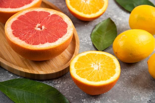 Feche foto de fatias de laranja e toranja na superfície cinza.