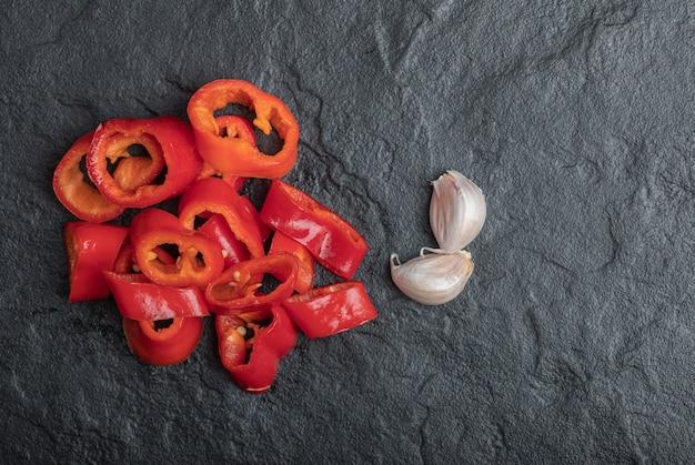 Feche foto de fatias de pimenta vermelha com alho em fundo preto.