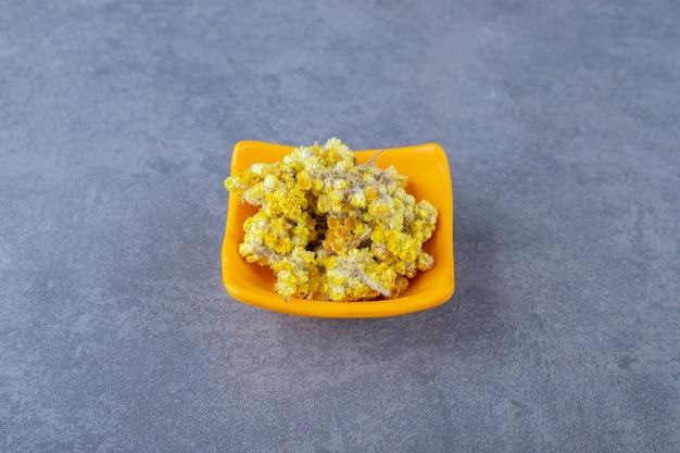 Feche foto de flores secas em uma tigela laranja sobre fundo cinza.