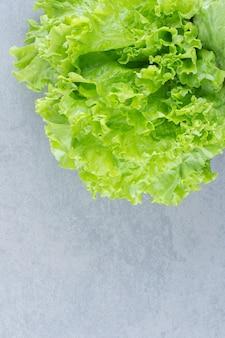 Feche foto de folhas de alface isoladas em fundo cinza.