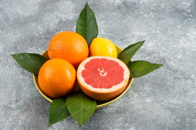 Feche foto de frutas frescas com folhas em uma tigela de cerâmica.
