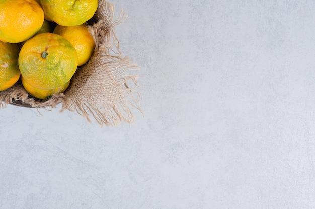 Feche foto de frutas tangerinas sobre fundo cinza.