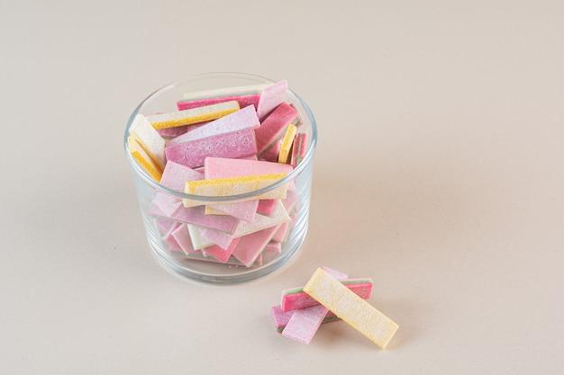 Feche foto de gomas coloridas em uma tigela de vidro com creme.