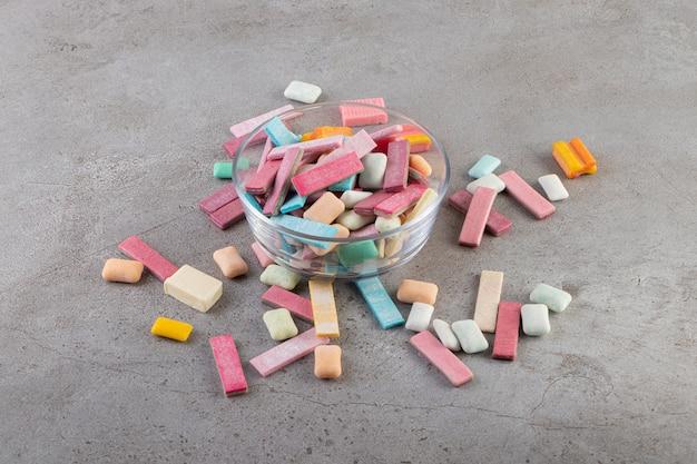 Feche foto de gomas coloridas em uma tigela de vidro sobre um fundo cinza.