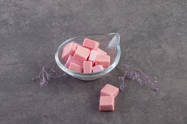 Feche foto de gomas-de-rosa na tigela de vidro.