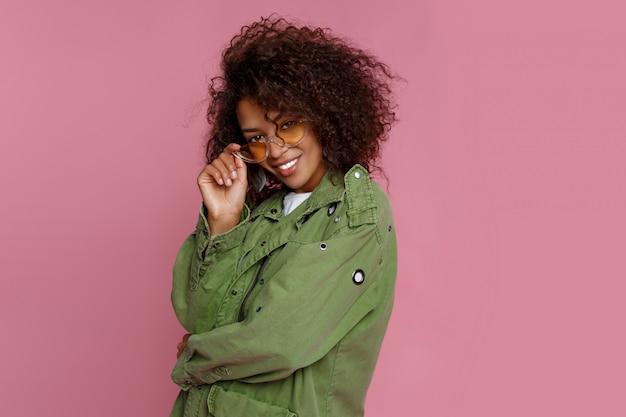 Feche foto de incrível garota africana encaracolada em fundo rosa. vestindo jaqueta verde da moda.